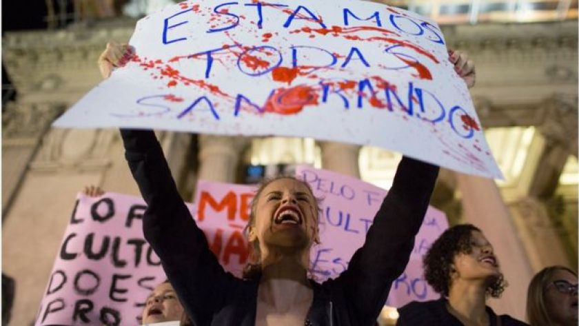 A woman shouts holding a banner that reads in Portuguese