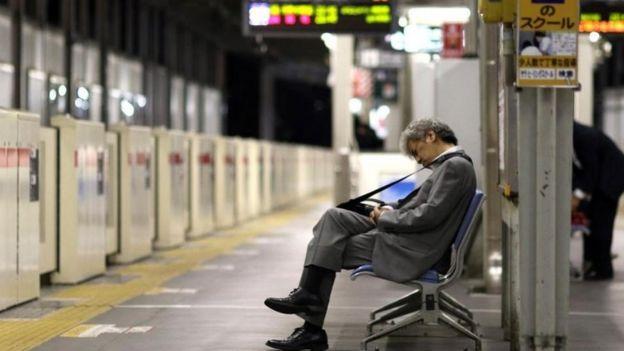 Un hombre dormido en un banco de una estación del metro