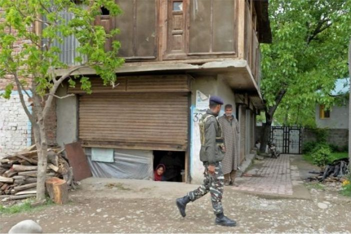 An Indian army soldier speaks with residents during an operation against suspected rebels in Turkwangam Lassipora in Shopian south of Srinagar on 4 May 2017