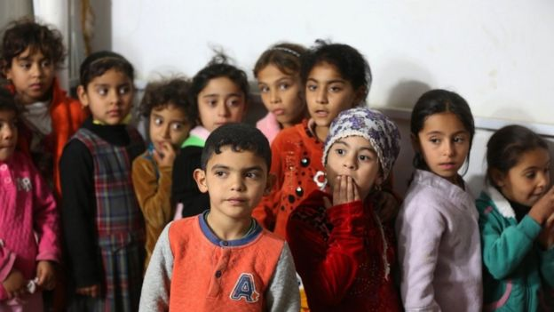 Iraqi children line up at a camp for displaced people, in the al-Shurta neighbourhood of west Baghdad, 14 Dec 2015