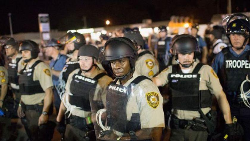 Police wearing riot gear in Ferguson, Missouri, stand in a line.