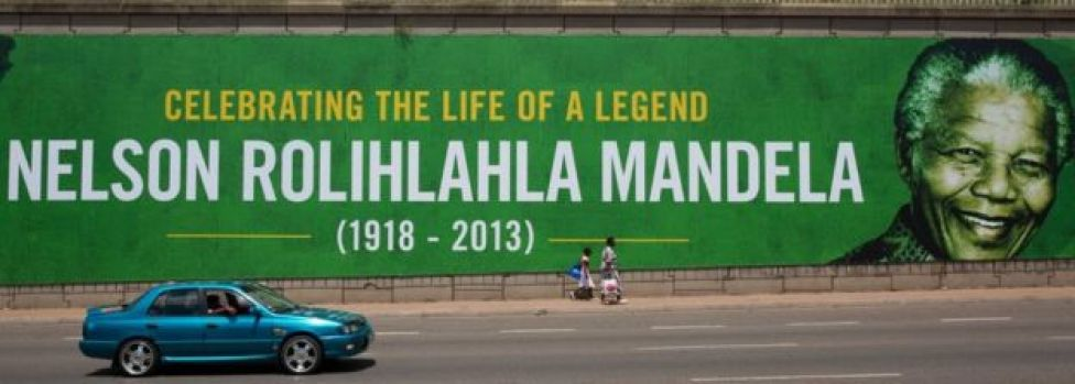 People walk past a giant poster of Nelson Mandela as the former South African president lies in state for a final day at Union Buildings on December 13, 2013 in Pretoria, South Africa.