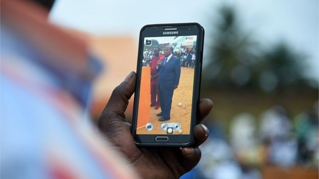 A supporter films with a smartphone Former Ivoirian Prime Minister and candidate for the upcoming presidential election Charles Konan Banny during a rally on 10 October, 2015 in Abidjan.