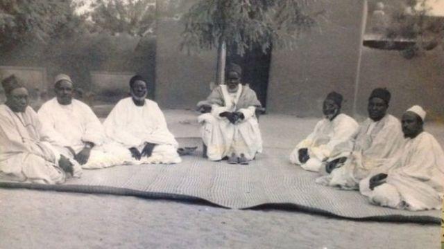 Shehu Umar Sanda Kyarimi Shehu of Dikwa Shehu na Borno a 1938-1967 tare da majalisarsa Waziri Ibrahim, Muqaddam, Mallam Buhari da, Mainin Kinandi Mustafa, Alkali Talba da Maaji Umar Yaqub