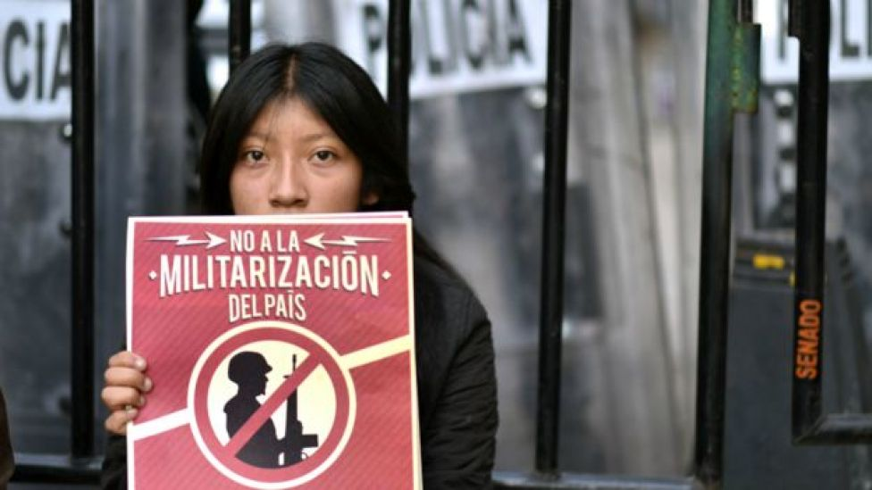 Joven con un cartel de protesta contra la militarización del país.