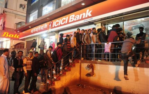 Indians queue to withdraw money from an ATM