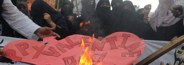 Pakistani women belonging to religious party Jamiat-e-Ulama Pakistan set fire to Valentine's Day cards during a protest against valentine's day in Karachi on February 14, 2012