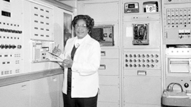 Mary Jackson holds a clipboard standing by a large computer
