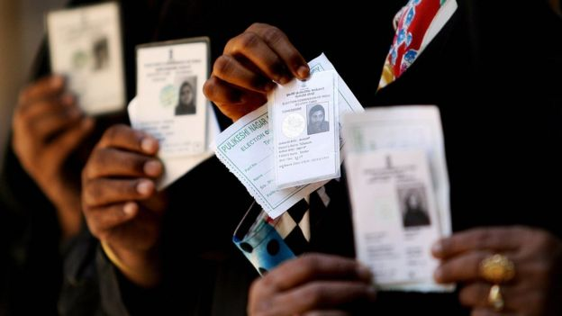 Voters show their voter's identity card as they wait in a queue to cast their vote for the Karnataka state election outside a polling booth in Bangalore on 10 May 2008.