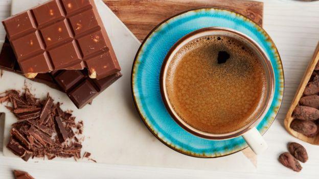 Barra de chocolate ao lado de uma xícara de café