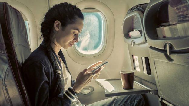 Una persona usando su teléfono para navegar en un vuelo