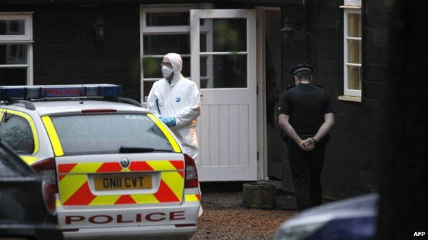 A police officer and forensic officer outside a house