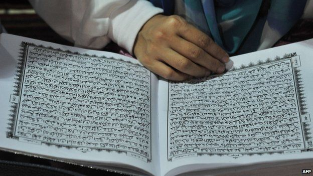 File photo: A woman reads a copy of the Koran