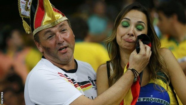 A Germany fan consoles a Brazil fan (R) during their 2014 World Cup semi-finals at the Mineirao stadium in Belo Horizonte