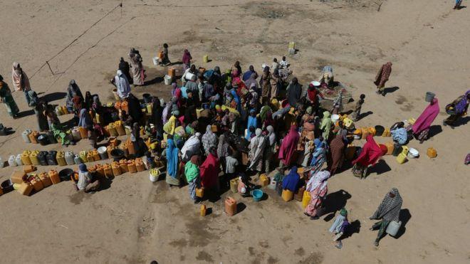 Mulheres e crianças reunidos em torno de um poço de água no campo de refugiados de Maiduguri, na Nigéria
