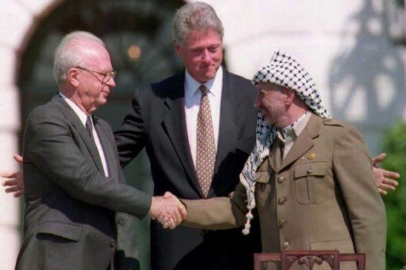 Prezydent USA Bill Clinton (w środku) stoi między liderem OWP Jaserem Arafatem (z prawej) izraelskim premierem Icchakiem Rabinem, jako dwoma uścisliwymi dłońmi.