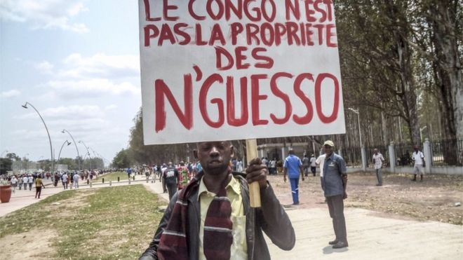 """A man holds a placard reading """"Congo is not the property of N""""Guesso"""" during an opposition demonstration in Brazzaville - 27 September 2015"""
