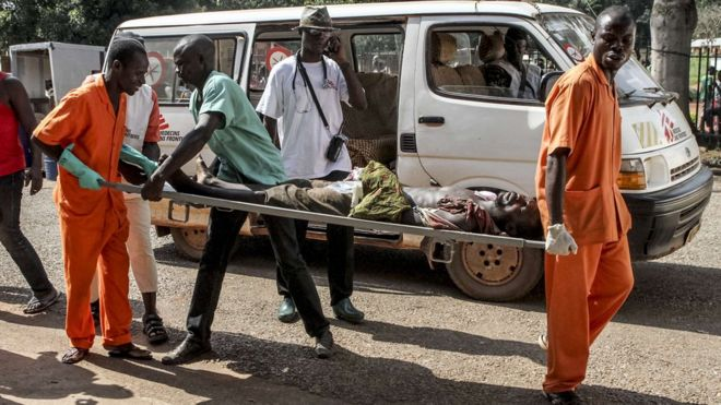 A wounded man is carried into the General Hospital in Bangui on September 26, 2015 after unknown assailants opened fire in the PK5 district, a neighbourhood with a majority of Muslim residents.