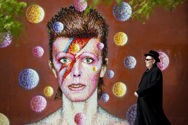 A man walks past a 3D wall portrait of British musician David Bowie, created by Australian street artist James Cochran, also known as Jimmy C, in Brixton, South London, on 19 June 2013. The artwork is based on the iconic cover for Bowies 1973 album, Aladdin Sane.