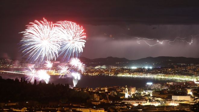 Panoramic shot of Nice, showing fireworks, the sea and a lightning storm in the distance, 14 July 2016.