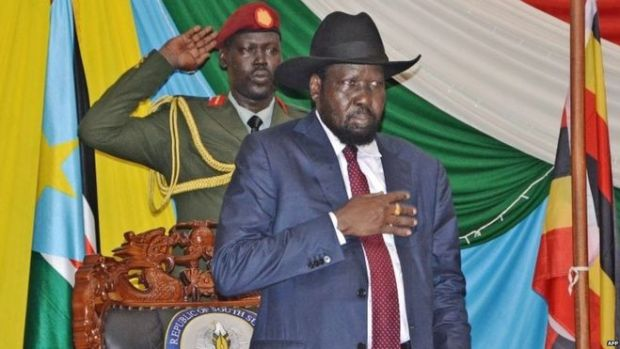 """South Sudan""""s President Salva Kiir (C) stands for South Sudan""""s national anthem before signing a peace agreement in the capital Juba, on August 26, 2015."""