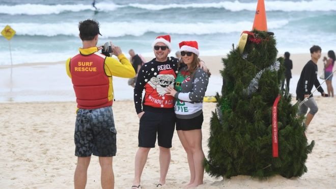 A Surf Life Saver takes a picture of a couple in front of a Christmas Tree on Bondi Beach in Sydney
