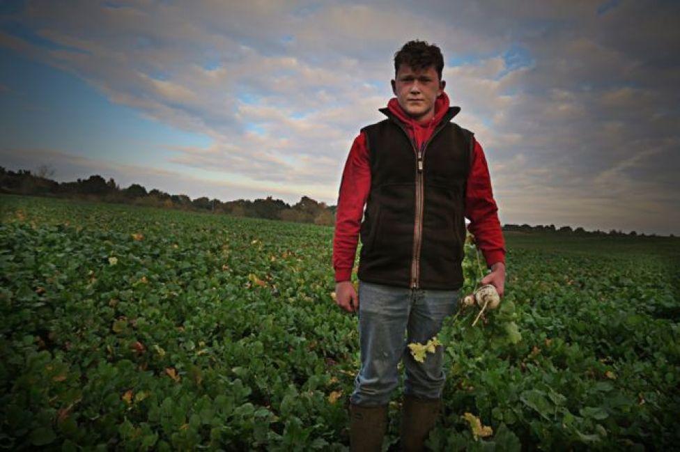 شاب يقف وسط أرض زراعية