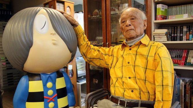 "Japanese 93-year-old comic artist Shigeru Mizuki sitting next to his famous character ""Kitaro"""
