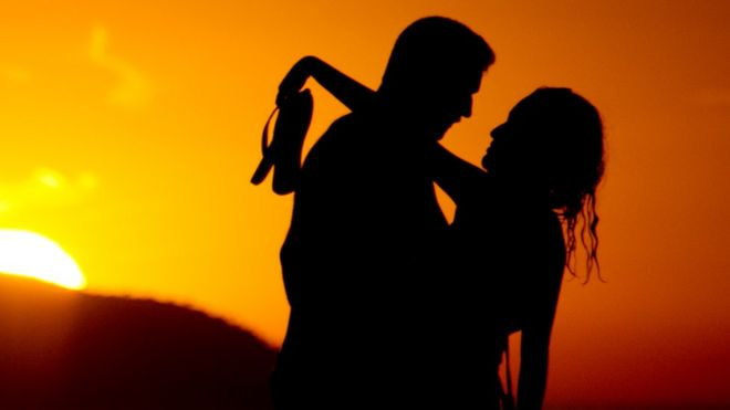 Couple on a beach at sunset, file pic