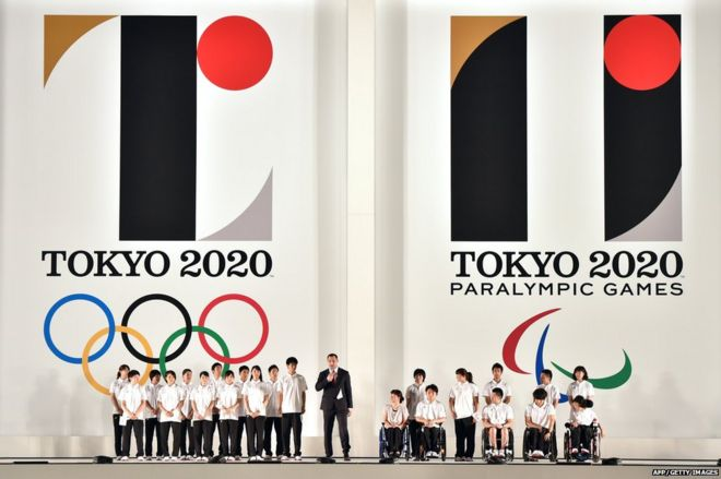 Hammer throw gold medallist Koji Murofushi (C), accompanied by young athletes, delivers a speech as the logo marks of the Tokyo 2020 Olympic (L) and Paralympic (R) Games are unveiled at the Tokyo city hall on 24 July 2015
