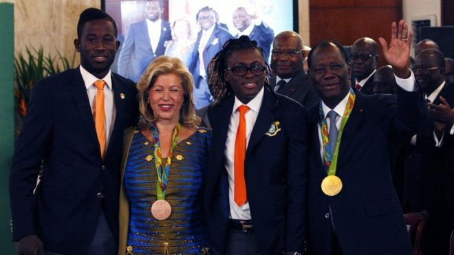 Ivorian President Alassane Ouattara (R) and his wife Dominique Ouattara pose with the Olympians.