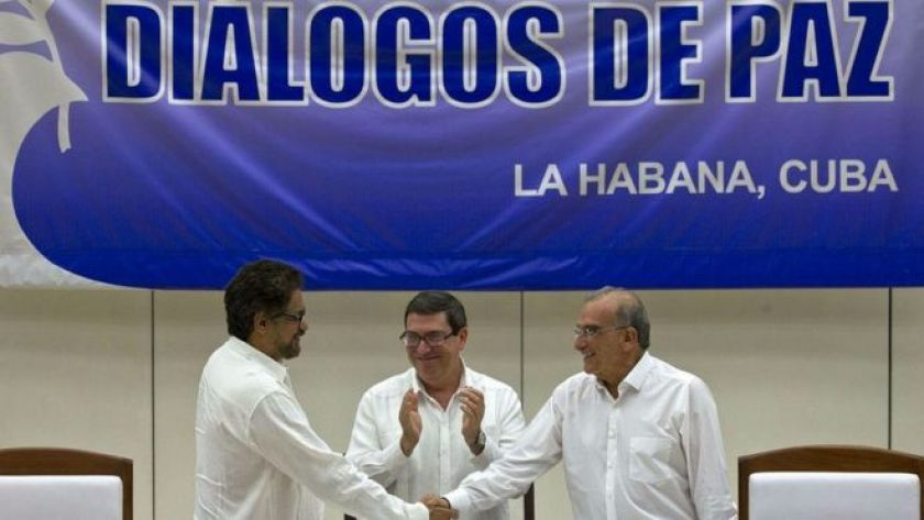 Humberto de la Calle, right, head of Colombia's peace negotiation team, shakes hands with Ivan Marquez, chief negotiator of Farc, left, while Cuban Foreign Minister Bruno Rodriguez, centre, applauds in Havana, Cuba. 24 August 2016