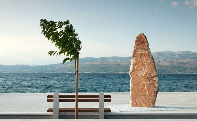 Una escultura, un árbol y un banco en frente del mar en Supetar, Croacia.