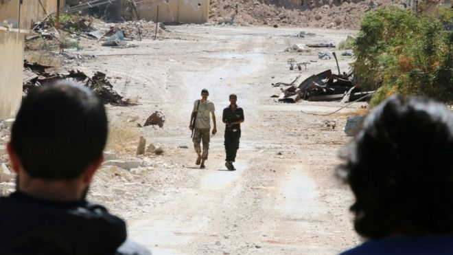 Rebel fighters walk by damaged buildings near Castello road in Aleppo, Syria, 16 September