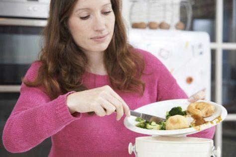 Mujer tirando sobras de comida a la basura