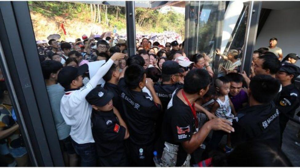Visitantes se aglomera a la entrada del puente colgante de vidrio del gran cañón de Zhangjiajie, provincia de Hunán.