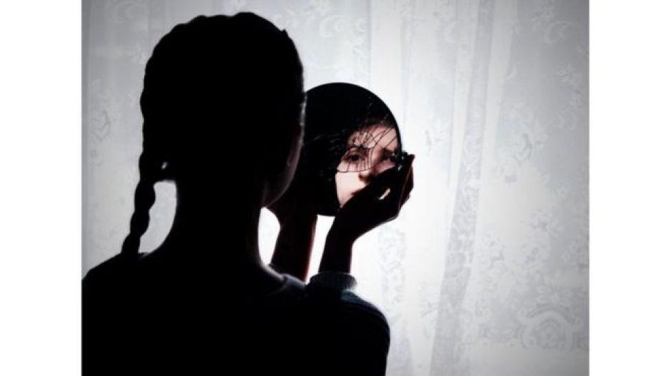 انعكاس صورة شابة في مرآة مكسورة