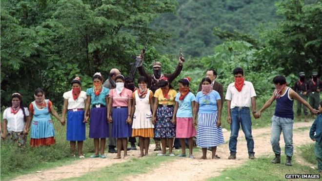 Subcomandante Marcos (centre, rear) stands in front of a group of Zapatista supporters on 7 January, 1996 in La Realidad, Mexico.