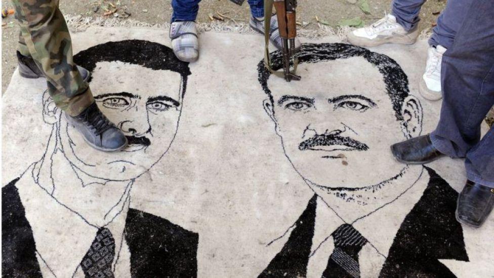 Rebeldes sirios pisan la imagen de los Asad en Ras-al-Ain en la frontera con Turquía.
