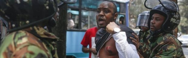 A Kenyan activist Boniface Mwangi protests against police officers as he shows his chest wounded by a tear gas canister during a demonstration against recent police brutality that killed some opposition protesters, in Nairobi, Kenya, 19 October 2017