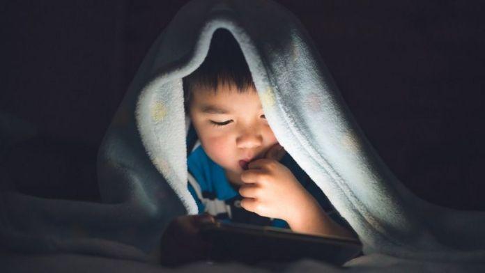 niño usando teléfono móvil