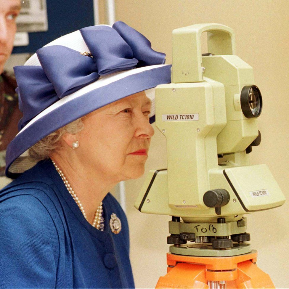 Queen Elizabeth II looking though a theodolite
