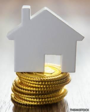 Un modelo de casa sobre una pila de monedas