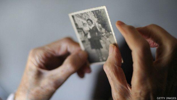Una señora sostiene una foto suya de cuando era una mujer muy joven