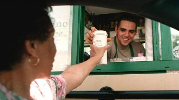 Una persona dándole una taza de café a otra