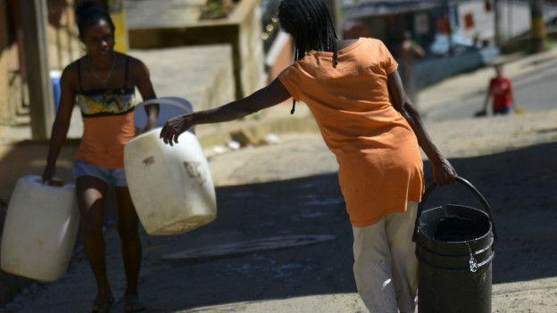 Dos mujeres cargan botes con agua en Colombia.