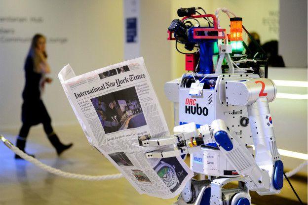 Un robot lee un periódico.
