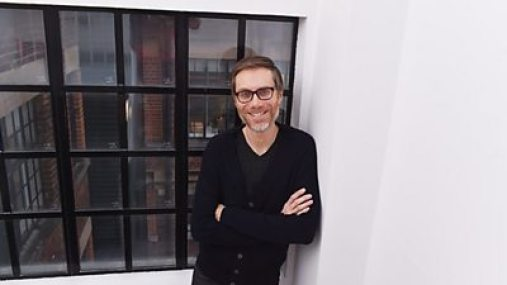 A man with a short beard and glasses wearing a black t-shirt and black cardigan standing by a window