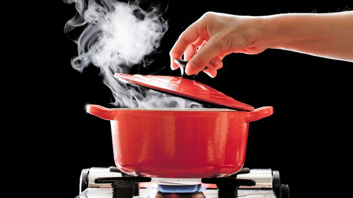 Woman putting a lid on a pan