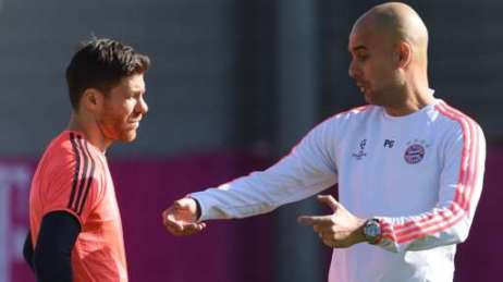 Xabi Alonso receives instructions from Pep Guardiola